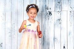 Счастливые усмехаясь пузыри мыла африканской девушки дуя на предпосылке деревянной стены Стоковая Фотография