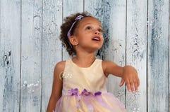 Счастливые усмехаясь пузыри мыла африканской девушки дуя на предпосылке деревянной стены Стоковые Фото