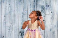 Счастливые усмехаясь пузыри мыла африканской девушки дуя на предпосылке деревянной стены Стоковое Изображение