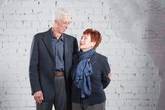 Счастливые усмехаясь старые пары стоя прижиматься совместно изолированный на белой предпосылке кирпича скопируйте космос Стоковая Фотография RF