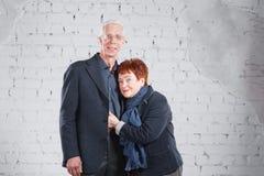 Счастливые усмехаясь старые пары стоя прижиматься совместно изолированный на белой предпосылке кирпича скопируйте космос Стоковые Изображения