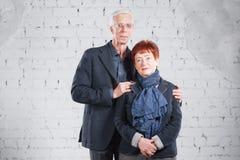 Счастливые усмехаясь старые пары стоя прижиматься совместно изолированный на белой предпосылке кирпича скопируйте космос Стоковое Фото