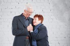 Счастливые усмехаясь старые пары стоя прижиматься совместно изолированный на белой предпосылке кирпича скопируйте космос Стоковые Фото