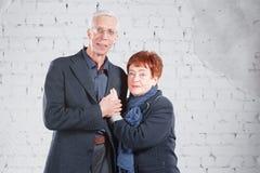 Счастливые усмехаясь старые пары стоя прижиматься совместно изолированный на белой предпосылке кирпича скопируйте космос Стоковая Фотография