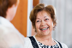 Счастливые удовлетворенные счастливые зрелые женщины сидя на софе Стоковое фото RF