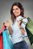 Счастливые улыбки женщины пока ходящ по магазинам стоковые фотографии rf