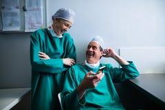 Счастливые хирурги взаимодействуя пока использующ мобильный телефон Стоковое Фото