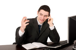 Бизнесмен сидя на столе говоря на телефоне. стоковое фото