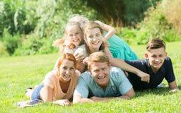 Счастливые человек и женщина при 4 дет лежа в парке Стоковое фото RF