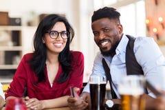 Счастливые человек и женщина с smartphone на баре Стоковое Фото