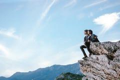 Счастливые человек и женщины сидят вниз на горе утеса в Черногории, f Стоковое Изображение RF