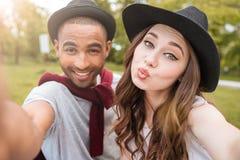 Счастливые шаловливые молодые пары делая selfie в парке Стоковые Изображения RF