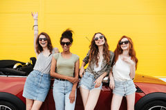 Счастливые эмоциональные 4 друз молодых женщин стоя близко автомобиль Стоковые Фото