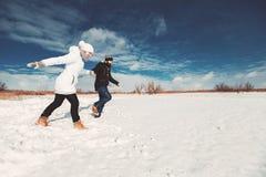 Счастливые любовники бежать через снег Стоковое фото RF