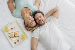 Счастливые любовники лежа на постельных принадлежностях с релаксацией Стоковое Фото