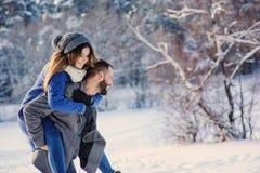 Счастливые любящие пары идя в снежный лес зимы, тратя рождество отдыхают совместно Внешняя сезонная деятельность Стоковая Фотография RF