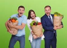 Счастливые люди держат сумки с здоровой едой, изолированные покупателей бакалеи Стоковые Изображения RF