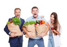 Счастливые люди держат сумки с здоровой едой, покупателей бакалеи Стоковая Фотография RF