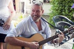Счастливые люди едят и играют гитару на партии Стоковая Фотография RF