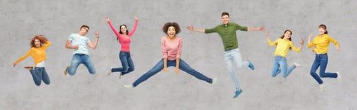 Счастливые люди или друзья скача в воздух над серым цветом Стоковое фото RF