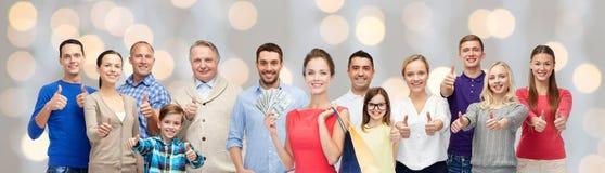 Счастливые люди при хозяйственные сумки показывая большие пальцы руки вверх Стоковое Изображение