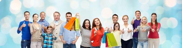 Счастливые люди при хозяйственные сумки показывая большие пальцы руки вверх Стоковые Фотографии RF