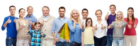 Счастливые люди при хозяйственные сумки показывая большие пальцы руки вверх Стоковая Фотография