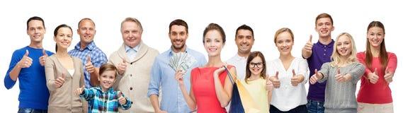 Счастливые люди при хозяйственные сумки показывая большие пальцы руки вверх Стоковое Фото