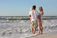 Счастливые люди семьи из трех человек играя в океане пока идя Alon стоковые изображения rf