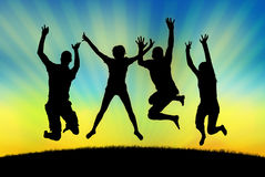 Счастливые люди скача в утеху на предпосылке захода солнца Стоковая Фотография RF