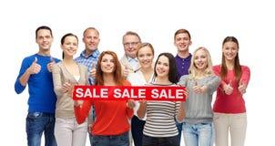 Счастливые люди с красной продажей подписывают показывать большие пальцы руки вверх Стоковые Изображения