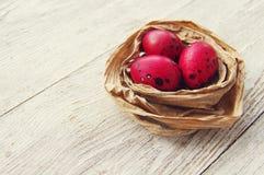 Счастливые яичка пасхи красные в декоративном гнезде Стоковые Изображения