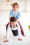 Счастливые excited дети имея потеху, ехать на задней части дома Стоковые Фото