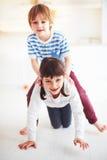 Счастливые excited дети имея потеху, ехать на задней части дома Стоковое Фото