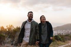Счастливые hikers идя в сельскую местность стоковое изображение
