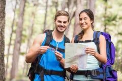 Счастливые hikers смотря камеру держа карту и компас Стоковые Изображения RF