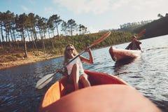 Счастливые kayakers гребя на озере Стоковые Изображения RF
