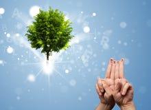 Счастливые smileys пальца с зеленым волшебным накаляя деревом Стоковое фото RF