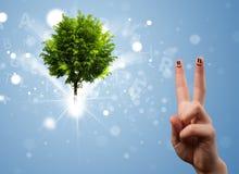 Счастливые smileys пальца с зеленым волшебным накаляя деревом Стоковые Фото