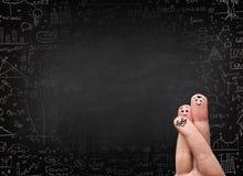 Счастливые smileys пальца с черной доской в предпосылке Стоковая Фотография RF
