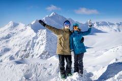 Счастливые snowboarders пар в горах Стоковые Изображения