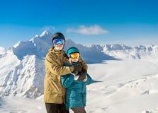 Счастливые snowboarders пар в горах Стоковая Фотография