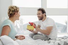 Счастливый давать супруга присутствующий к его жене стоковое изображение