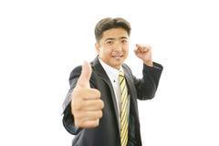 Счастливый азиатский бизнесмен показывая большие пальцы руки поднимает знак стоковое изображение rf