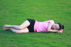 Счастливый азиатский китайский сон женщины на траве Стоковое Изображение