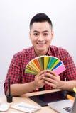 Счастливый азиатский мужской график-дизайнер держа вентилятор цвета в его руке Стоковые Фото