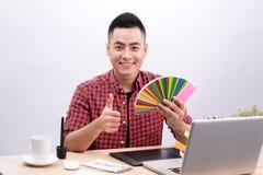 Счастливый азиатский мужской график-дизайнер держа вентилятор цвета в его руке Стоковая Фотография RF