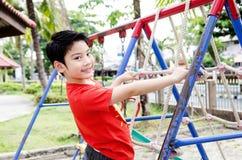 Счастливый азиатский ребенок играя на спортивной площадке Стоковая Фотография RF