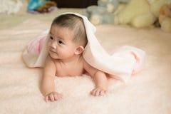 Счастливый азиатский ребенок положенный на кровать стоковая фотография