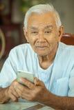 Счастливый азиатский старший человек используя мобильный телефон Стоковые Фото